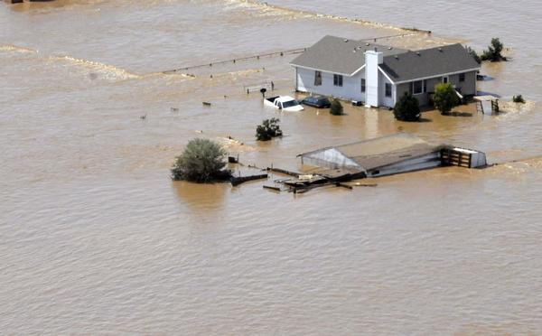 The South Platte River surrounds a home west of Kersey, Colo. Five people have been confirmed dead since the floods began Wednesday.