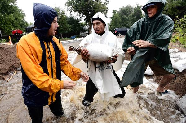 Residents pass sandbags to reinforce a dam in Boulder, Colo., as rain continues to fall. More than 1,200 people were unaccounted for amid the flooding.