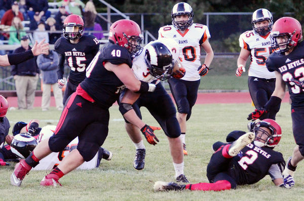East Jordan senior nose guard Ben Walton (left) wraps up Harbor Springs senior running back David Walker during Fridays Lake Michigan Conference contest at Boswell Stadium in East Jordan. The Red Devils defeated the Rams, 20-7, to move to 3-0 overall, 1-0 league.