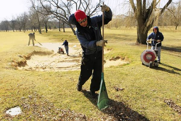 In this file photo, Gerardo Contreras and fellow groundskeepers for the Winnetka Golf Club in Winnetka clear greensand sand traps March 6, 2012 in preparation for the opening of the course.