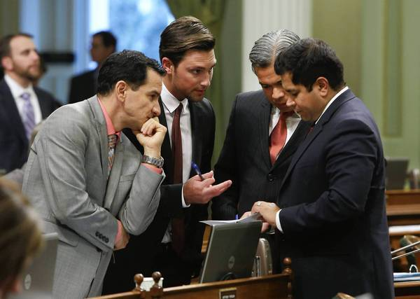 Democratic Assembly members, from left, Anthony Rendon of Lakewood, Ian Calderon of Whittier, Rob Bonta of Alameda and Jimmy Gomez of Los Angeles, huddle during the Assembly session at the Capitol on Wednesday.