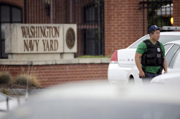 A law enforcement officer keeps bystanders back from the scene of a shooting at the Washington Navy Yard in Washington.