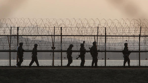 South Korean soldiers patrol along a barbed-wire fence near the border village of Panmunjom, in the demilitarized zone between North and South Korea, on March 26, 2013.