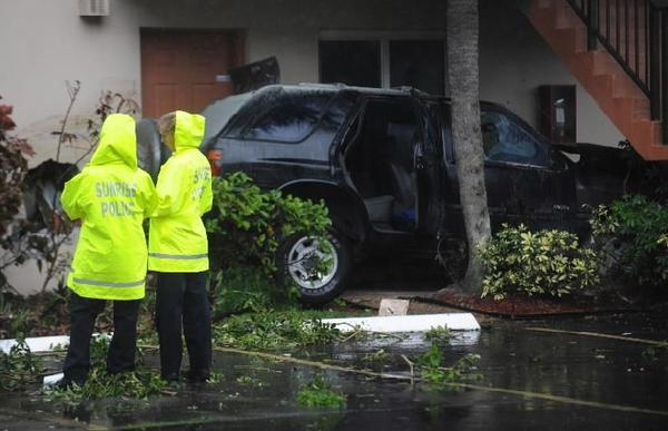 Investigators at the scene of a crash in which an SUV ran into the first floor of an apartment building on Del Lago Circle in Sunrise on Monday, Sept. 16, 2013.