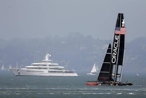 Larry Ellison's Oracle Team USA catamaran trains for the America's Cup sailing event in San Francisco Bay. In the background is Ellison's yacht.
