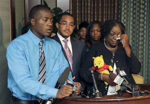 Willie Ferrell, left, talks about his older brother Jonathan A. Ferrell, who was shot to death early Saturday. Ferrell's mother, Georgia Ferrell, is at right, and family attorney Christopher Chestnut is at center.