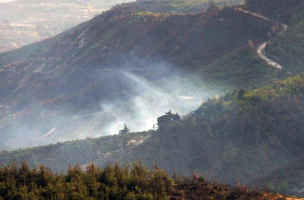 Smoke rises from the site where Turkish authorities say a Syrian military helicopter was shot down after it entered Turkish airspace.
