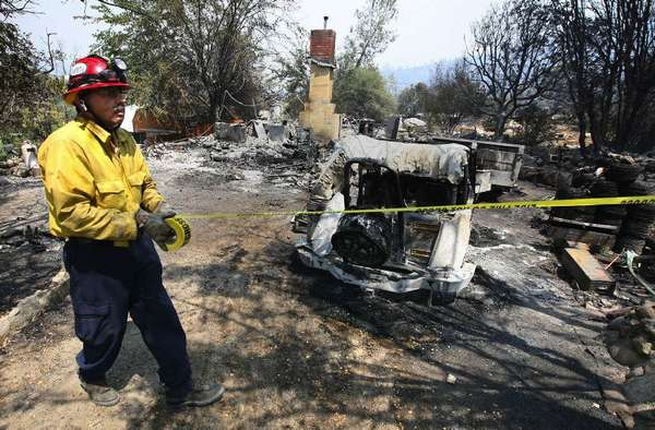 A firefighter at a destroyed Riverkern house, part of a 2010 wildfire in the Sequoia National Forest. The U.S. government has settled a lawsuit against Southern California Edison related to an earlier 2007 fire in the same area.