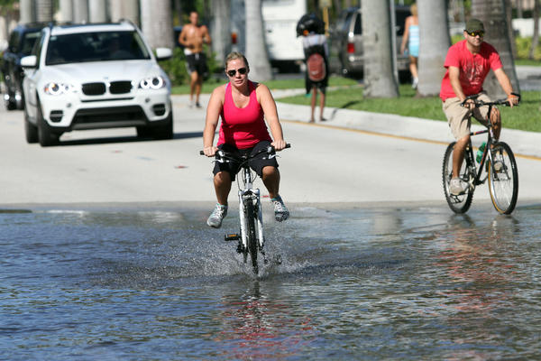 Jennifer Hare and Kevin Clegg, vacationing from Hilton Head, SC, ride through a puddle left from high tide flooding on Las Olas Boulevard in Fort Lauderdale on Oct. 16, 2012.