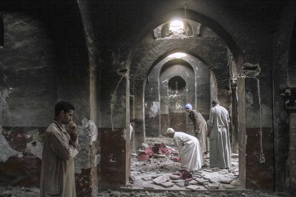 Villagers clean up the chapel in a monastery that was looted and burned by Islamists in Dalga, Egypt, on Sept. 3. Security forces on Monday swept into the town, making arrests and seizing weapons caches in an offensive targeting Islamists.