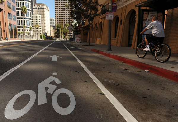 A byclist rides on the sidewalk despite the new commuter bike lane on 7th Street in downtown Los Angeles.
