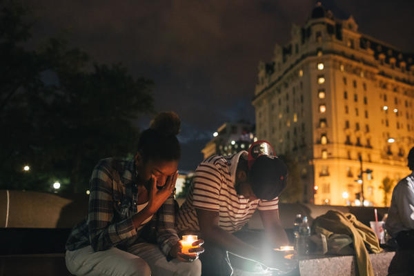 The vigil, during which organizers called for stricter gun laws, was in remembrance of the 12 victims killed in a shooting at the Washington Navy Yard earlier in the day.