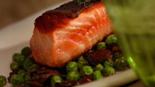Crispy-skinned wild salmon with braised spring peas and mushrooms