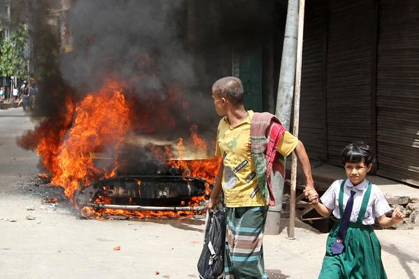 Pedestrians walk past a vehicle set afire during protests of the death sentence handed down against Abdul Quader Molla, a leader of the opposition Jamaat-e-Islami party