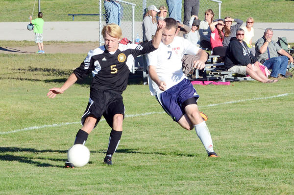 Harbor Springs junior John Bailey (left) takes a shot on goal as Boyne City senior Corey Bohnet defends during Mondays Lake Michigan Conference match at the Boyne City Middle School field.