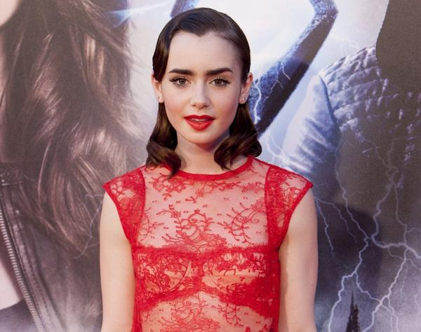 "English actress Lily Collins, shown at the premiere of the film ""The Mortal Instruments: City of Bones,"" leads McAfee's list of ""most dangerous"" cyber celebrities -- figures whose popularity is used by hackers to trick fans into downloading malware."