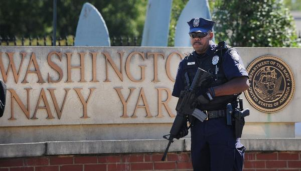 A police officer stands guard Tuesday at the front gate of the Washington Navy Yard in Washington, where a gunman killed 12 people before being shot dead by law enforcement.