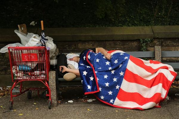 Amid the halting recovery, homelessness has increased in cities such as New York. Above, a homeless man sleeps under an American flag blanket on a park bench in Brooklyn.