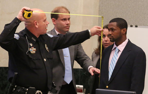 Ocoee police Cpl. Dewey Mullan, left, measures the height of defendant Nolan Bernard ,right,as defense attorney Andrew Clark,2nd,left, and co-counsel Alyssa Salman looks on.