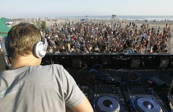 A large crowd sways to the beats of DJ Robbie Rivera at the Wet Electric Festival at Huntington State Beach.