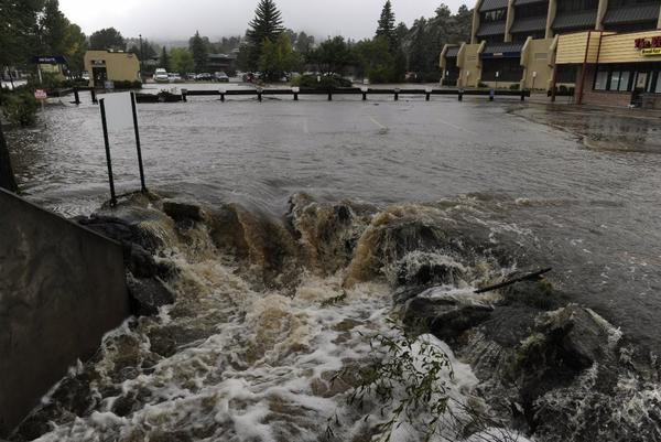 Estes Park, Colo., has been devastated by heavy flooding. Here, water pours out of a parking lot, overwhelming a culvert heading under the roadway.