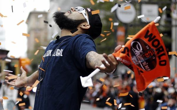 San Francisco Giants pitcher Sergio Romo looks up as confetti falls during the baseball team's World Series victory parade in San Francisco.