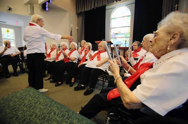 Members of the handbell choir at Bridgewater at Waterman Village in Mount Dora, hold practice. Residents have found the handbell choir to be a way to share their love of music in a way that bridges any language, age or cognitive barriers.