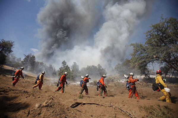 Inmate firefighters based at a camp in Azusa fight a Tehachapi wildfire.