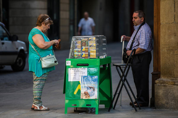 A vendor sells lottery tickets in the Catalonian town of Manresa. Authorities in the Galician town of La Coruna are searching for the owner of a $6.3-million winning ticket who can identify where and when the lucky numbers were purchased.