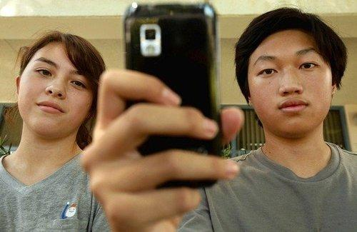 Young Cho, left, here with Hoover High classmate Christopher Chung, thinks the school district's monitoring program goes too far.