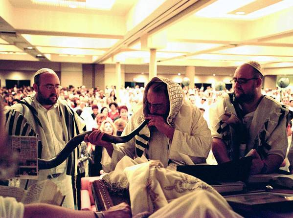 Rabbi Philip Berg, with his two sons at either side, blows the shofar on Rosh Hashana in November 2001 before a gathering of 2,000 kabbalah adherents.