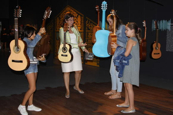 Visitors to A Tres Bandas peruse the dozen different types of guitars that hang in an art installation.