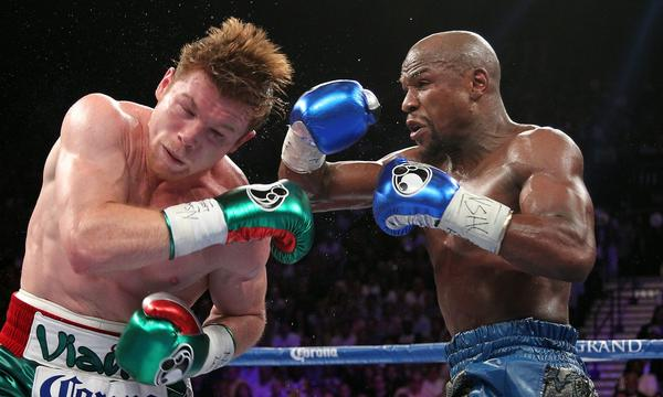 "Floyd Mayweather Jr., right, delivers a blow to Saul ""Canelo"" Alvarez during their fight on Saturday night. Mayweather won by decision, but judge C.J. Ross scored it a draw."