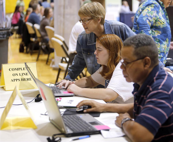 Roberta Thompson, of Mellette, top center, helps her daughter Melissa, center, fill out an on line application at Tuesday's Job Fair at the Aberdeen Civic Arena. In the foreground is Larry Owens, of Aberdeen, who was also applying for a job on line. photo by john davis taken 9/17/2013