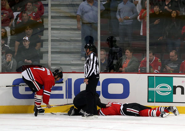 Blackhawks defenseman Brent Seabrook attends to injured teammate Mike Kostka.