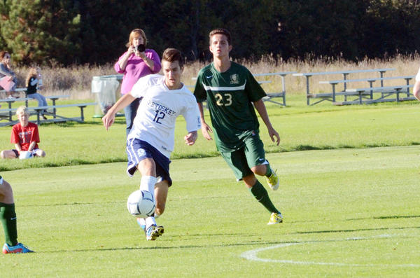 Petoskey junior Phil Brown (12) moves the ball up the field in front of Traverse City West junior Cameron Sipple (23) during Tuesday's Big North Conference match at the Click Road Soccer Complex. The Titans defeated the Northmen, 1-0.