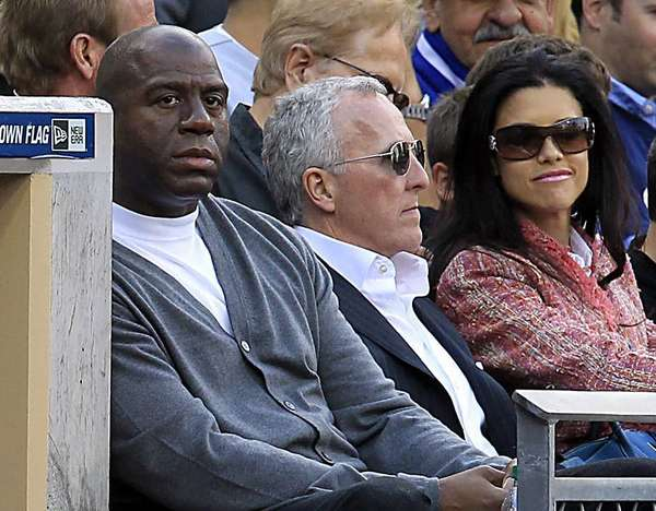 Magic Johnson, left, and Frank McCourt watch the Dodgers play on April 5, 2012.