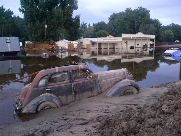 A car swallowed by mud in Loveland, Colo.