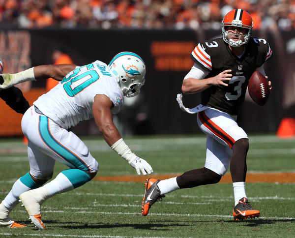 Cleveland Browns quarterback Brandon Weeden scrambles away from Miami Dolphins defensive end Olivier Vernon.