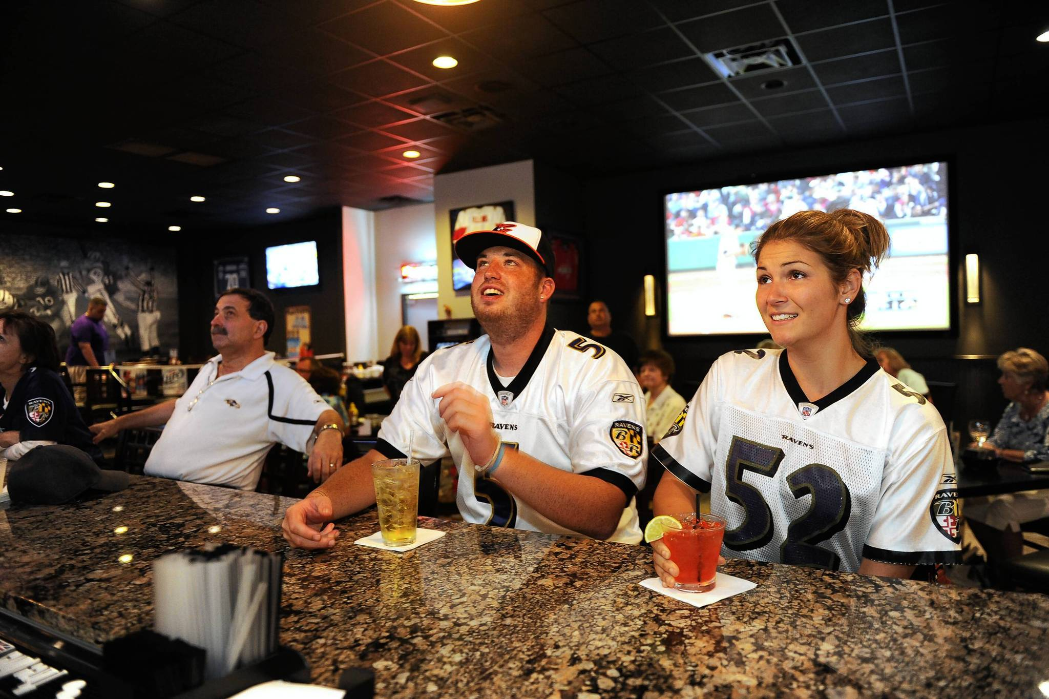 Kyle Kramer and Briana Spangler react to the Orioles game at Playoff Bar and Grill.