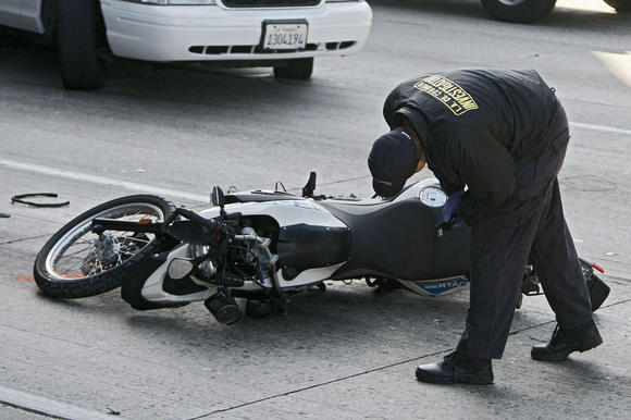 A Los Angeles County Coroner Investigator examines the scene of a fatal motorcycle crash on the northbound 5 Freeway under the 134 Freeway overpass in the Glendale-Burbank area on Tuesday morning, Sept. 17, 2013. Traffic was backed up for miles on the 134 and 5 freeways.