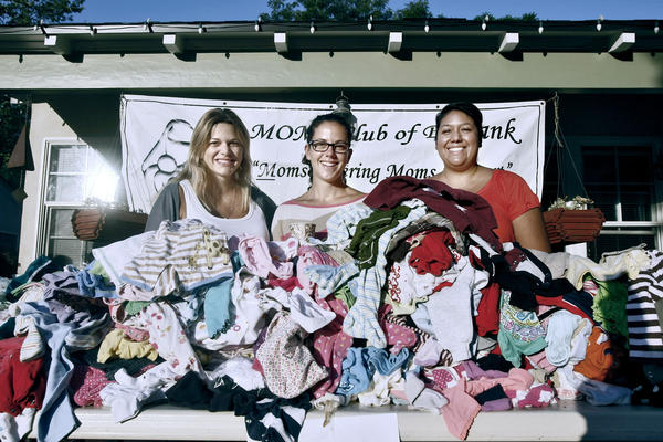 Moms Club of Burbank members, left to right, Lisa Dietrick, Karen Bowlin and Lisa Krueger, with piles of baby clothes ready to sell at their bi-annual yard sale to benefit the Mother 2 Mother Fund, in Burbank on Saturday, Sept. 14, 2013. The club had about 4,500 items, mostly for young children, for sale.