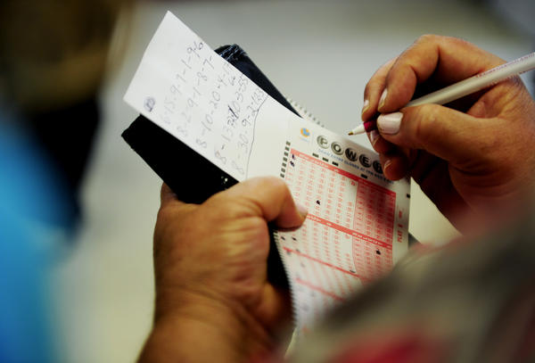 A lottery player fills out Powerball tickets at Bluebird Liquor in Hawthorne before August's $425-million drawing.