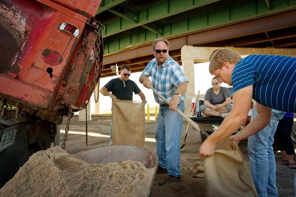 Tim Unruh, of Paxton, Neb., center, shovels sand into a bag as residents fill sandbags along the South Platte River in Ogallala, Neb. Colorado floodwaters were flowing into the state Wednesday, with some flooding in rural areas.