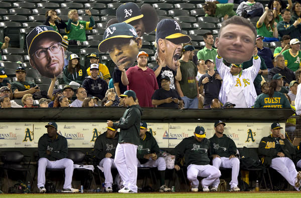 Athletics fans hold up cutouts of players in the stands during a game against the Houston Astros in Oakland.