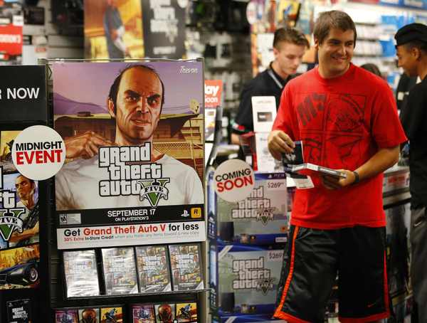 "Game enthusiasts purchase the latest release of ""Grand Theft Auto V"" after the game went on sale at the Game Stop store in Encinitas, California."