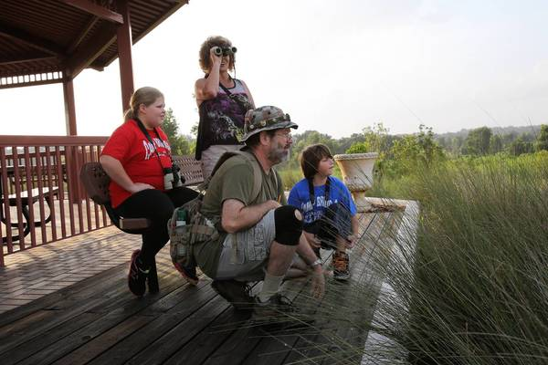 """Mike Barnett leads a hike with Paige, 11, Jason Pinault, 8 and Sandra Becker at PEAR Park in Leesburg. Cornerstone Hospice and Palliative Care has launched a new bereavement program called the """"Family Nature Walks."""""""