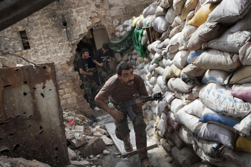 Rebel fighters duck as they run behind a barricade to avoid being fired at by Syrian regime forces in the Old City's front line in Aleppo.
