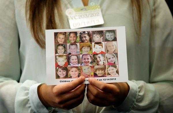 Kyra Murray holds a photo with victims of the shooting at Sandy Hook Elementary School during a press conference at the Capitol calling for gun reform legislation.