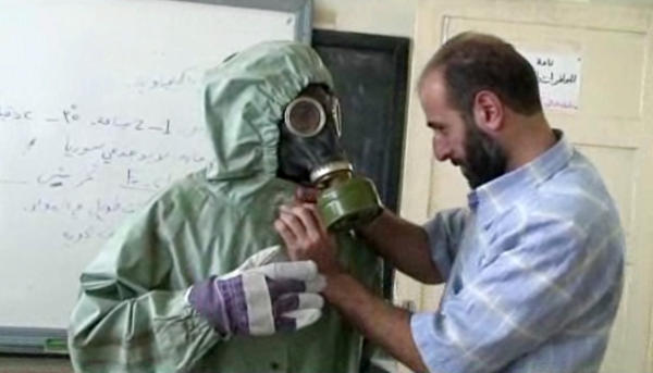 A volunteer adjusts a student's gas mask and protective suit during training in the Syrian city of Aleppo on how to respond to a chemical attack.
